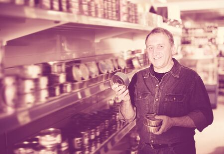 Portrait of glad man buying a preserves at the grocery store Banco de Imagens