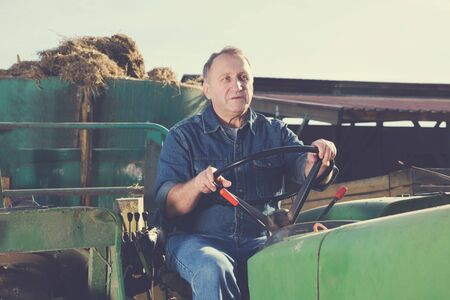 Portrait of serious male farmer sitting in tractor Imagens - 124741728