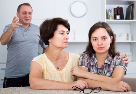 Senior woman sitting with young unhappy woman and trying to help indoors