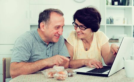 Laughing mature man and woman discussing while looking at laptop together at the home. Focus on both persons