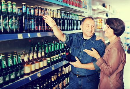 Portrait of an elderly cheerful glad couple buying a beer at the grocery store