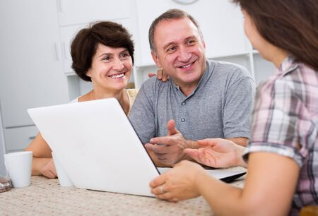 Positive couple listening to woman with laptop indoors