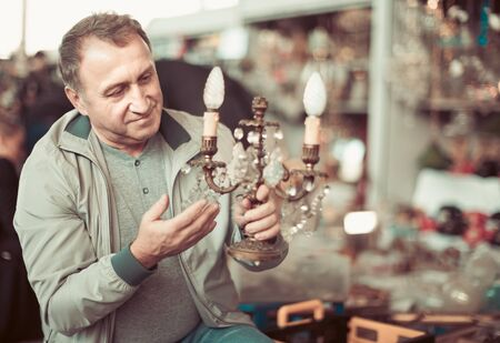 Senior man customer choosing vintage souvenir at flea market