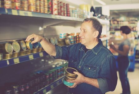 Portrait of an elderly man buying a preserves at the grocery store Banco de Imagens