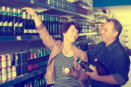 Portrait of  an elderly positive european couple buying a beer at the grocery store