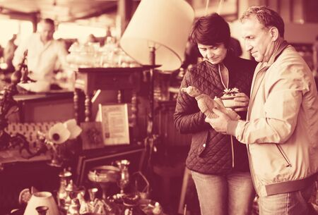 cheerful mature spouses buying retro handicrafts on indoor flea market Stock Photo