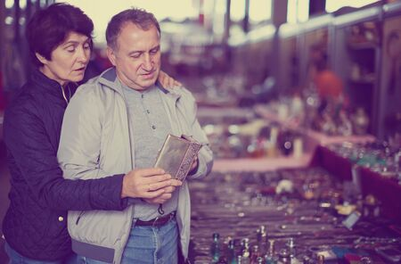 Glad man and woman choosing interesting souvenirs at traditional flea market