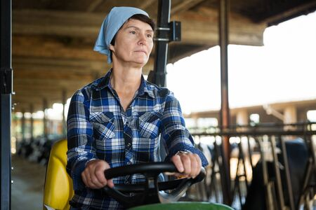 Portrait of mature female worker sitting in tractor on farm Imagens - 124741865