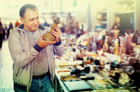 Positive glad cheerful  man choosing interesting souvenirs at traditional flea market