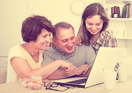 Smiling adult daughter with her mature parents searching documents on laptop at home