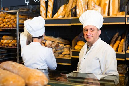 Happy staff posing with  fresh baguettes and buns in bakery