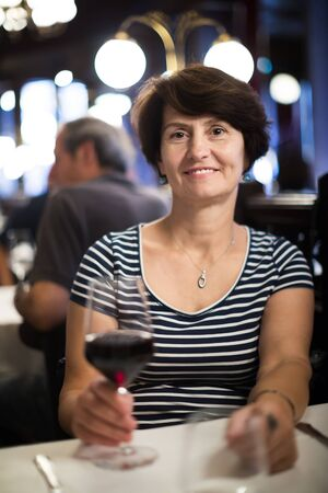 Positive woman sits at table at restaurant and holds glass with wine Imagens