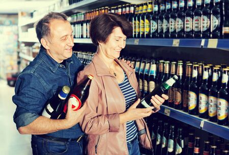 Portrait of an elderly smiling glad couple buying a beer at the grocery store