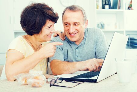 cheerful elderly couple looking on laptop screen  indoors at home together.  Focus on man 版權商用圖片