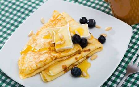 Sweet crepes served with soft creamy brie, berries of blueberry, roasted pine nuts and topped with honey