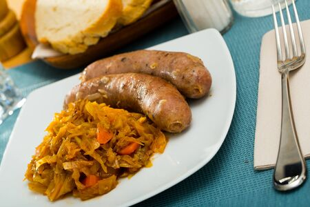 Roasted sausages served with side dish of cabbage stewed with carrot Stock Photo