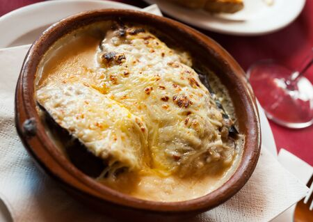 Spanish cuisine. Delicious meat stuffed eggplants topped with grated cheese served in clayware