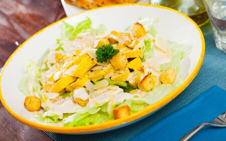 Appetizing Caesar salad with chicken breast, lettuce and toast