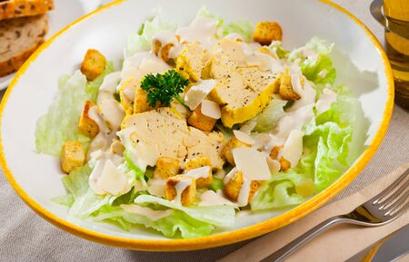 Caesar salad with grilled chicken on a white plate