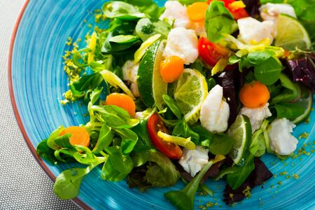 Tasty salad with cod and fresh greens. Recipe: marinate 200gr of chopped cod fillets in lime juice and black pepper. Serve with lettuce, carrots, sliced limes. Dress with oil and balsamic