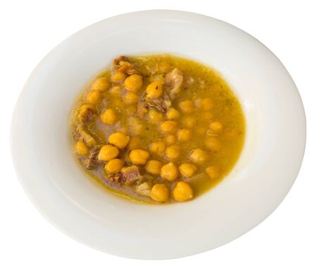 Stewed chickpeas with Iberian bacon served on white plate, traditional Spanish. Isolated over white background