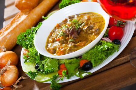 Delicious goulash of chicken hearts served on platter with fresh vegetables