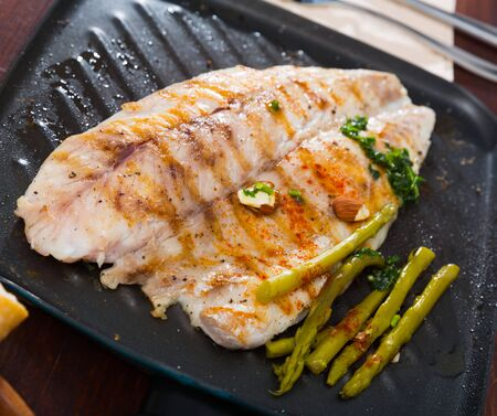 Plate of tasty fish dish – slices of roasted sea bass with asparagus Banco de Imagens
