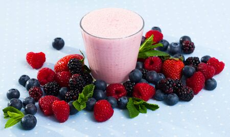 Smoothie with yogurt and berries on background with fresh blueberries, raspberries, strawberries, blackberries and mint