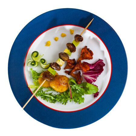 Top view  of tasty shish kebab from chicken hearts with  avocado and   fried chanterelles  at plate. Isolated over white background