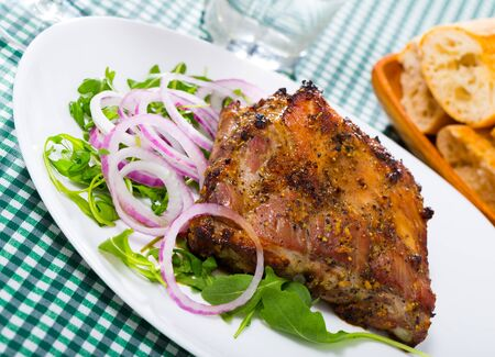 Roasted rack of pork served with fresh salad leaves and purple onion rings