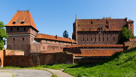 Brick walls and towers of medieval Malbork Castle in sunny summer day, Poland