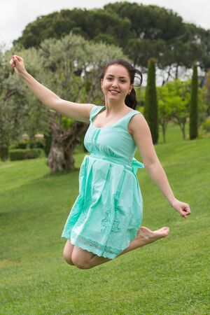 happy young european  brunette female in dress jumping at the park