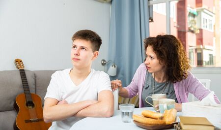 Portrait of troubled teen boy and his mother scolding him in home interior Imagens - 124966680