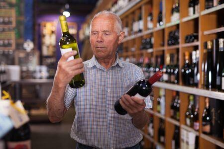 Positive grey-haired elderly man choosing wine in modern wineshop