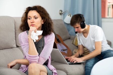 Frustrated mother sitting on sofa at home while her teenage son absorbed of social networks on laptop