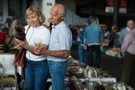 Elderly family choose handmade vase at flea market
