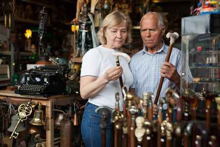 Elderly man and woman examine rare walking stick on flea market