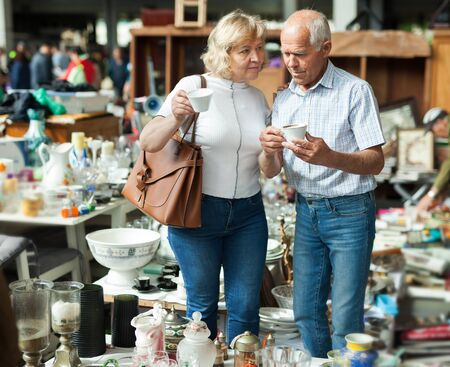 Mature family couple choosing vintage dishes on street market