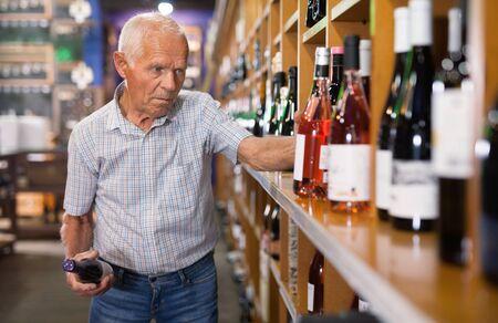 Positive happy cheerful smiling grey-haired elderly man choosing wine in modern wineshop