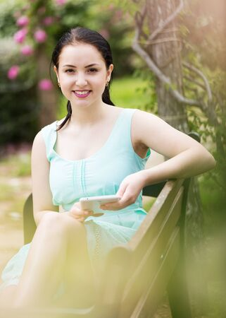 smiling young female using digital tablet outdoors