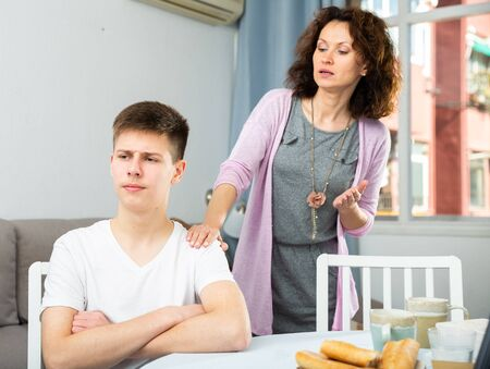 Portrait of offended teenager sitting at home while mother berating him