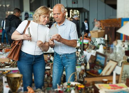 Mature man and his wife are visiting market of old things