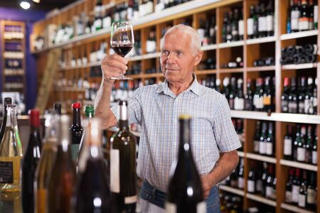 Confident elderly man tasting red wine in wine store before buying Фото со стока