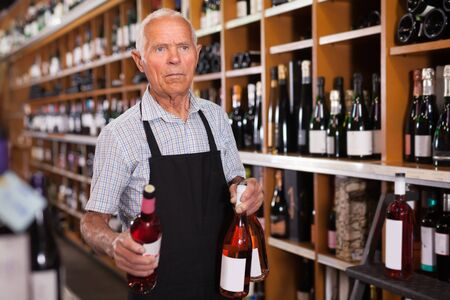 Fine male vintner working in modern wine shop, arranging wine bottles on racks Banco de Imagens - 124967068