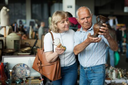 Smiling mature spouses buying retro handicrafts on flea market Stock Photo