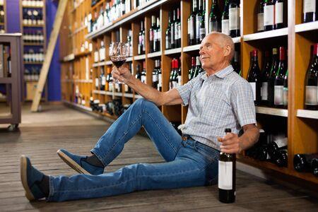 Portrait of cheerful positive  senior man sitting on floor in winery tasting room, drinking red wine Reklamní fotografie