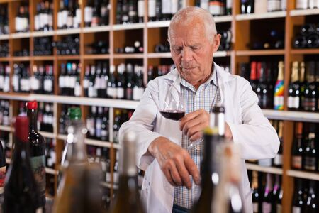 Older man wine producer inspecting quality of red wine, standing in wineshop on background with shelves of wine bottles
