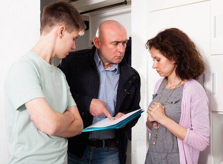 Debt collector and frustrated mother and teenage son with overdue payment at doorway
