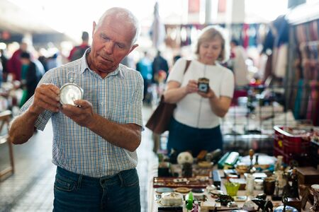 Loving mature couple buys alarm clock on flea market