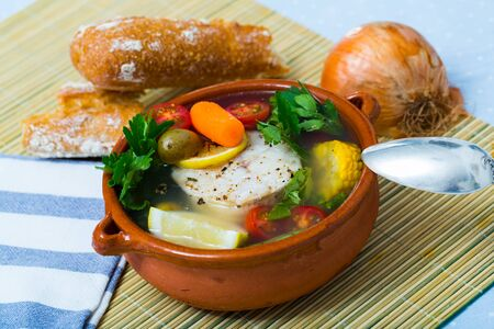 Recipe of pottage of fisherman: boil cod head for broth. Add potatoes, carrots, shallots, corn, fish steak 200 g, salt, pepper. Bring to oven, cook for 40min at temperature of 200 deg Stock Photo